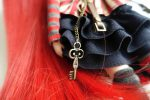 Detail of Cheshire Cat's corset's key pendant that hangs over her skirt.